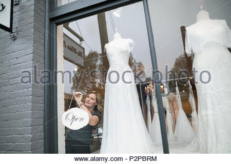 Bridal boutique owner hanging open sign in window - Stock Photo