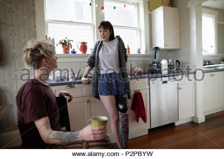 Young woman amputee drinking coffee, talking with boyfriend in kitchen - Stock Photo