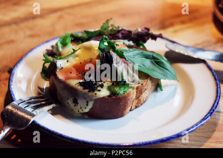 Bruschetta with poached egg and greens on the table in the cafe - Stock Photo