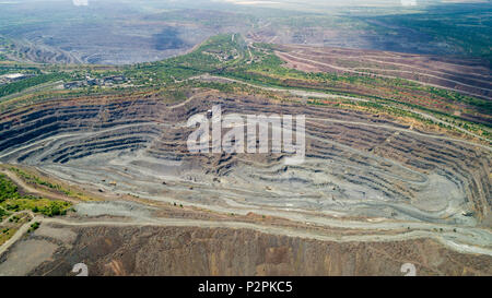 Aerial view of opencast mining quarry with lots of machinery at work. - Stock Photo