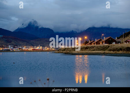 The 'Bahìa Encerrada' reflects some street lights in Ushuaia. In the background lies the small harbor, followed by the partly hidden mountains. - Stock Photo