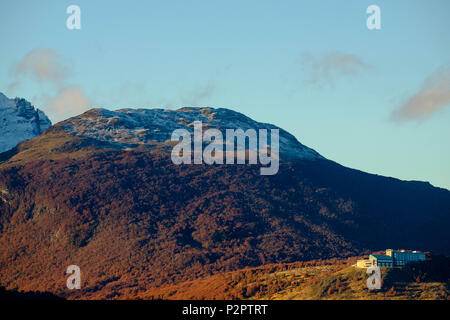 An expensive hotel is built on a hill that looks down on Ushuaia, Argentina. Late sunlight enlightens the autumn forest. - Stock Photo