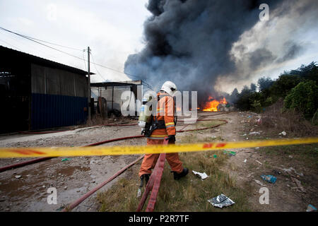 A fireman is pulling a firehose towards a burning factory in Sungai Petani. The fire broke at 1:00 PM and razed a plastic recycling centre, a plywood processing factory and a casket factory. More than 20 fire trucks were dispersed to control the massive fire due to wind condition and flammable products. - Stock Photo