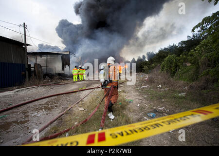 Sungai Petani, Kedah, Malaysia. 16th June, 2018. A fireman is pulling a firehose towards a burning factory in Sungai Petani. The fire broke at 1:00 PM and razed a plastic recycling centre, a plywood processing factory and a casket factory. More than 20 fire trucks were dispersed to control the massive fire due to wind condition and flammable products. Credit: Aizzat Nordin/SOPA Images/ZUMA Wire/Alamy Live News - Stock Photo
