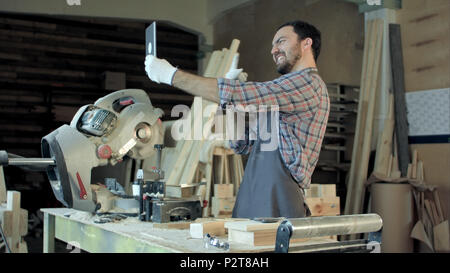 Carpenter makes selfie near woodworking machines in carpentry shop. - Stock Photo