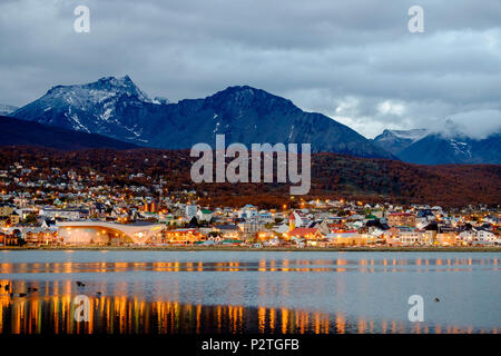 The 'Bahía Encerrada' reflects the city lights of Ushuaia. It is automn and the trees have a strong color. Ushuaia is often very cloudy. - Stock Photo