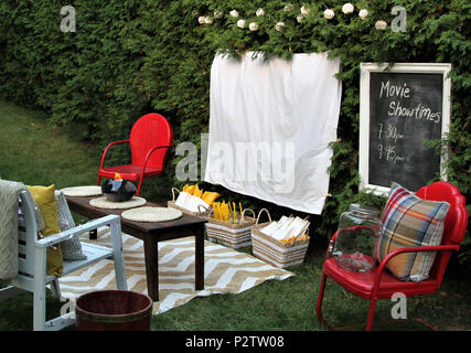 White sheet ready for a movie night outdoors with food and chairs - Stock Photo