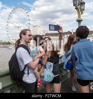 London, UK: July 25, 2016: Tourists take a photograph on Westminster Bridge with a view of Thames River behind them. - Stock Photo