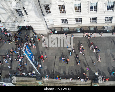 London, UK: July 25, 2016: Tourists walk beneath the London Eye on London's South Bank. The area is a popular tourist location. - Stock Photo
