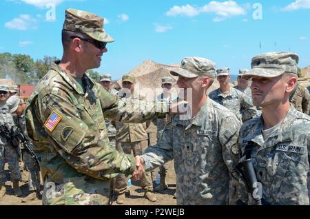 Brig. Gen. William Edwards, the Oregon Army National Guard's land component commander, gives his coin to Soldiers from Bravo Company, 3rd Battalion, 116th Cavalry Brigade Combat Team, during exercise Saber Guardian 2016, August 5, at the Romanian Land Forces Combat Training Center in Cincu, Romania. Saber Guardian is a multinational military exercise involving approximately 2,800 military personnel from ten nations including Armenia, Azerbaijan, Bulgaria, Canada, Georgia, Moldova, Poland, Romania, Ukraine and the U.S. The objectives of this exercise are to build multinational, regional and joi - Stock Photo