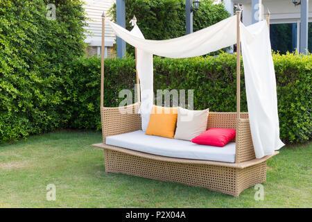 Modern sofa  wicker and color pillows in the garden. - Stock Photo
