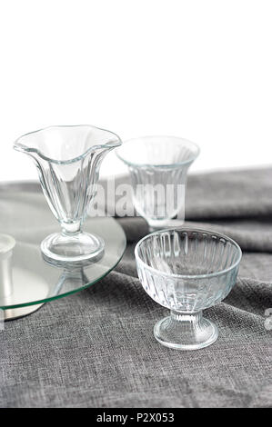 3 Clean glass bowls for ice cream, with different texture, are on the table with a gray tablecloth - Stock Photo
