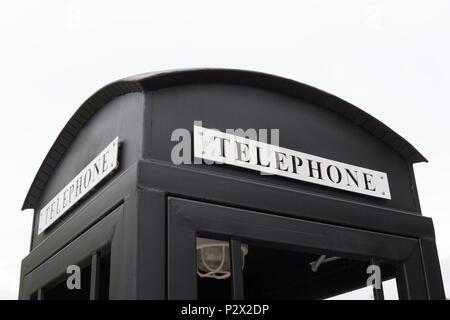 Vintage big black pay phone on white sky. - Stock Photo