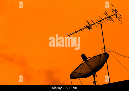 Television antenna and satellite dish for communication broadcast on the roof with sunset sky, twilight time, silhouette orange background, effect lig - Stock Photo
