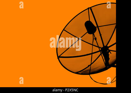 Satellite dish for communication broadcast on the roof with sunset sky, twilight time, silhouette orange background, effect light, with copy space. - Stock Photo
