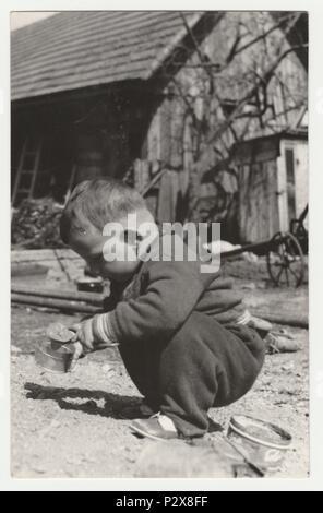 THE CZECHOSLOVAK SOCIALIST REPUBLIC - CIRCA 1970s: Vintage photo shows a small boy plays in the backyard.  Retro black & white  photography. - Stock Photo