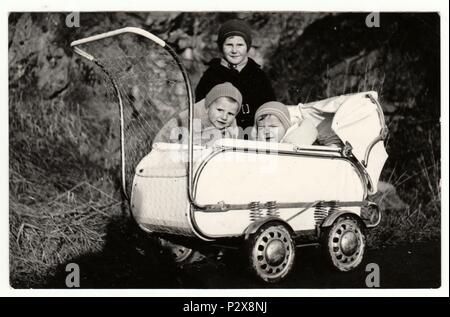 THE CZECHOSLOVAK SOCIALIST REPUBLIC - CIRCA 1950s: Vintage photo shows  small children and baby in the pram (carriage) in the wintertime.  Retro black & white  photography. - Stock Photo