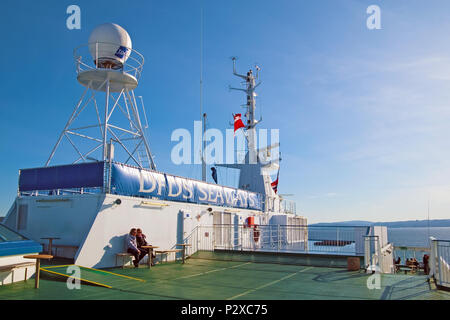 OSLO, NORWAY - APRIL 12, 2010: People sit near mast and navigation system on the deck of ferry DFDS SEAWAYS company - Stock Photo