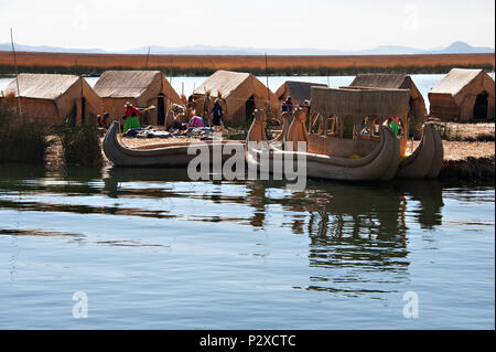 Reed boats that are used to transport tourists to and from Uros island known also as the floating islands in Peru, South America - Stock Photo