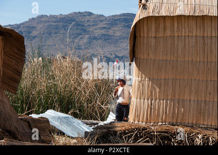 A resident child living on the reeds on Uros island known also as the floating islands in Peru, South America - Stock Photo