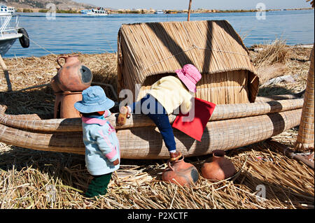 Local resident children climbing on to a reed boat on Uros island known also as the floating islands in Peru, South America - Stock Photo