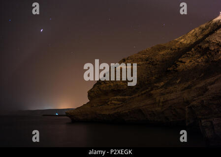 The arabian night on the sea of Oman, with reflections, stars and steep cliffs - 2 - Stock Photo