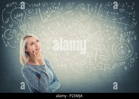 Portrait of thoughtful young woman looking up and imagining, has many ideas, dreaming. Decision making process. Positive puzzled girl thinking of a so - Stock Photo