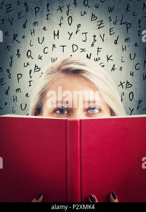 Close up portrait of pretty student girl hiding behind a red opened book with lating alphabet letters on the background. Mysterious and shy woman keep - Stock Photo