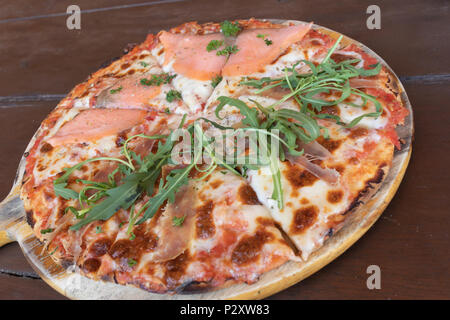 Delicious baked Salmon Italian pizza from the oven for lunch or dinner meal lie on the wooden tray on the wooden table - Stock Photo