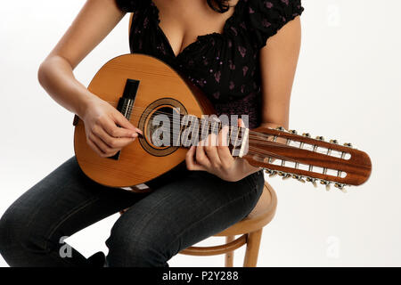 Young woman playing the Bandurria or 12 string spanish mandolin with a plectrum - Stock Photo