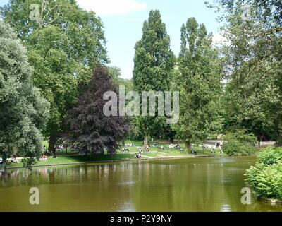 People relaxing lakeside at Park Buttes Chaumont on a warm, sunny Saturday afternoon in northeast Paris, France - Stock Photo