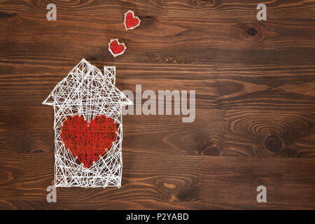 Home sweet home. Handmade home symbol with heart shape on wooden background with copy space - Stock Photo