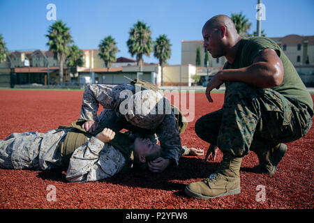 U.S. Marine Corps Lance Cpl. Matthew Little, left an electrician with Special Purpose Marine Air-Ground Task Force Crisis Response-Africa, listens and feels for irregular breathing during a combat lifesaver course at Naval Air Station Sigonella, Italy, August 4, 2016. During the four-day course, Marines learned to recognize injuries, perform the appropriate procedures and control the patient to prolong survivability until help arrives. U.S. Marines and Sailors assigned to Special Purpose Marine Air-Ground Task Force-Crisis Response-Africa Command support operations, contingencies and security  - Stock Photo
