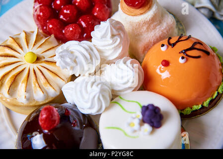 Different appetizing tasty cakes on a plate close-up. - Stock Photo