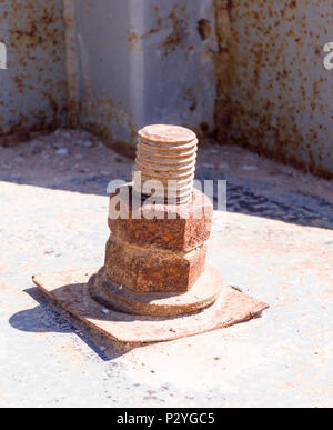 rusty iron screw with nut at sunny day. industrial concept - Stock Photo