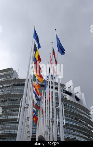 STRASBOURG, BR, FRANCE - JUNE 13, 2018: Row of Flags waving at the European Parliament, European Parliament in Strasbourg under overcast sky - Stock Photo