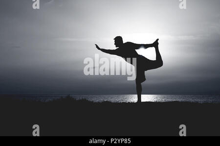 Silhouette of Young Man Practicing Yoga. Sunset on the Seacoast. Standing Bow Pose or Dandayamana Dhanurasana. - Stock Photo