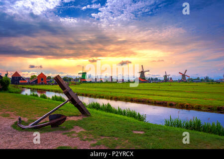 Traditional village at sunset, with dutch windmills, bridge and river on Zaanse Schans, Holland, Netherlands. - Stock Photo