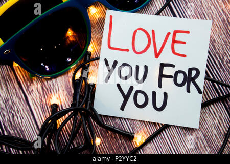 Love You For You handwritten on white note paper and love written in red color and further written in black color. Two Glasses with wooden background  - Stock Photo