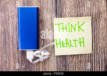 Power bank and note with the words Think Health are present on a woody surface. state of physical, mental and social well-being is mentioned in the im - Stock Photo