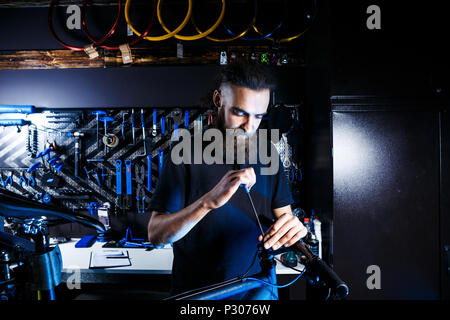 Theme sale and repair of bicycles. Young and stylish with a beard and long hair, a Caucasian man uses a tool to set up and repair a bike in a store. Business owner at work - Stock Photo