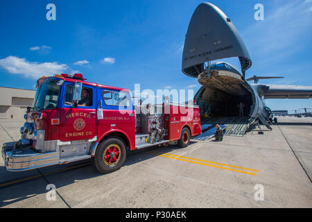 Loadmasters with the 439th Airlift Wing, Air Force Reserve Command, load a 1982 Mack 1250 GPM pumper fire truck onto a C-5B Galaxy at Joint Base McGuire-Dix-Lakehurst N.J., August 12, 2016. The truck will be flown to Managua, Nicaragua. Master Sgt. Jorge A. Narvaez, a traditional New Jersey Air National Guardsman with the 108th Security Forces Squadron, was instrumental in getting the truck donated to a group of volunteer firefighters in Managua. The truck donation is done through the Denton Program, which allows U.S. citizens and organizations to use space available on military cargo aircraft - Stock Photo