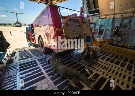 Loadmasters with the 439th Airlift Wing, Air Force Reserve Command, secure a 1982 Mack 1250 GPM pumper fire truck onto a C-5B Galaxy at Joint Base McGuire-Dix-Lakehurst N.J., August 12, 2016. The truck will be flown to Managua, Nicaragua. Master Sgt. Jorge A. Narvaez, a traditional New Jersey Air National Guardsman with the 108th Security Forces Squadron, was instrumental in getting the truck donated to a group of volunteer firefighters in Managua. The truck donation is done through the Denton Program, which allows U.S. citizens and organizations to use space available on military cargo aircra - Stock Photo