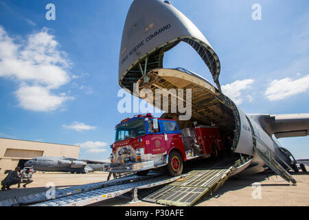 Loadmasters with the 439th Airlift Wing, Air Force Reserve Command, load a 1982 Mack 1250 GPM pumper fire truck onto a C-5B Galaxy at Joint Base McGuire-Dix-Lakehurst N.J., Aug. 12, 2016. The truck will be flown to Managua, Nicaragua. Master Sgt. Jorge A. Narvaez, a traditional New Jersey Air National Guardsman with the 108th Security Forces Squadron, was instrumental in getting the truck donated to a group of volunteer firefighters in Managua. The truck donation is done through the Denton Program, which allows U.S. citizens and organizations to use space available on military cargo aircraft t - Stock Photo