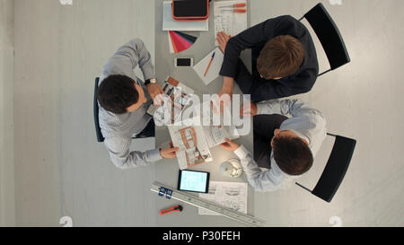 Top view of Colleagues interior designers discussing data with blank screen new modern computer laptop and pro digital tablet with sample material - Stock Photo