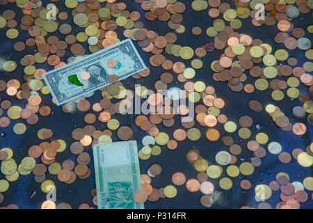 Money including coins and paper money in a wishing well - Stock Photo