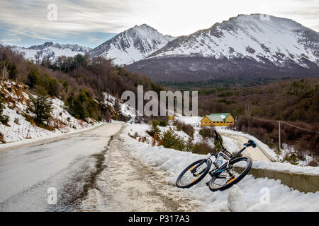 A mountainbike is resting next to the road in between the Martial Glacier and the city of Ushuaia. Snow has made the descent more dangerous. - Stock Photo