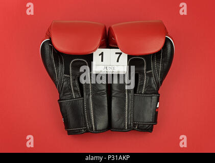 Black boxing gloves keep calendar with the number 17 June on red background. Greeting card concept to celebrate Father's day - Stock Photo