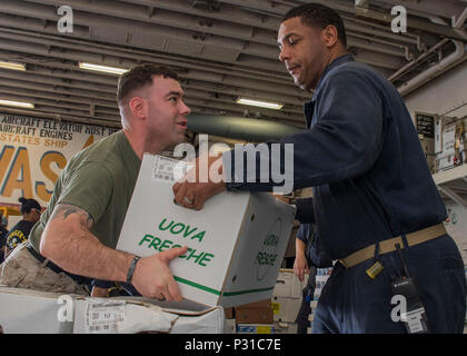 160822-N-LG762-240 MEDITERRANEAN SEA (Aug. 22, 2016) Marine Staff Sgt. William Taylor and Chief Culinary Specialist John Carter stack boxes of eggs in the hangar bay aboard the amphibious assault ship USS Wasp (LHD 1) during a replenishment-at-sea Aug. 22, 2016.  Wasp is deployed with the Wasp Amphibious Ready Group to support maritime security operations and theater security cooperation efforts in the U.S. 6th Fleet area of operations. (U.S. Navy photo by Mass Communication Specialist 3rd Class Zhiwei Tan/Released) - Stock Photo