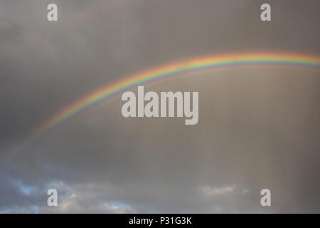 Background of bright colorful rainbow against dark grey clouds on a rainy autumn day - Stock Photo